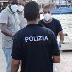Giovane migrante sbarca a Lampedusa indossando una maglia della Polizia di Stato.